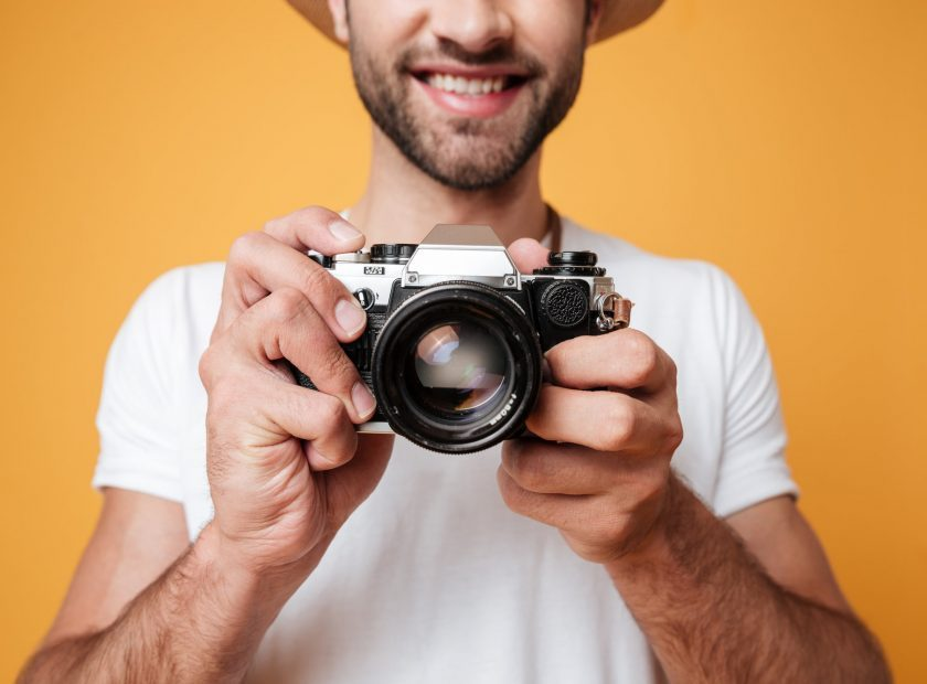 Close up shot of young man taking photo with retro camera